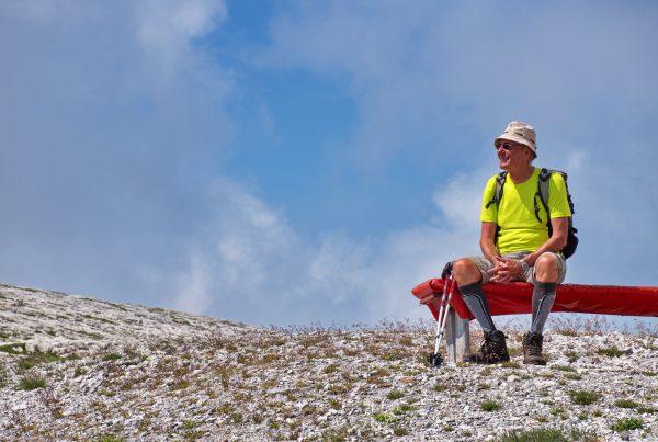 Portrait of senior hiker sitting on the bench in Brenta Dolomites