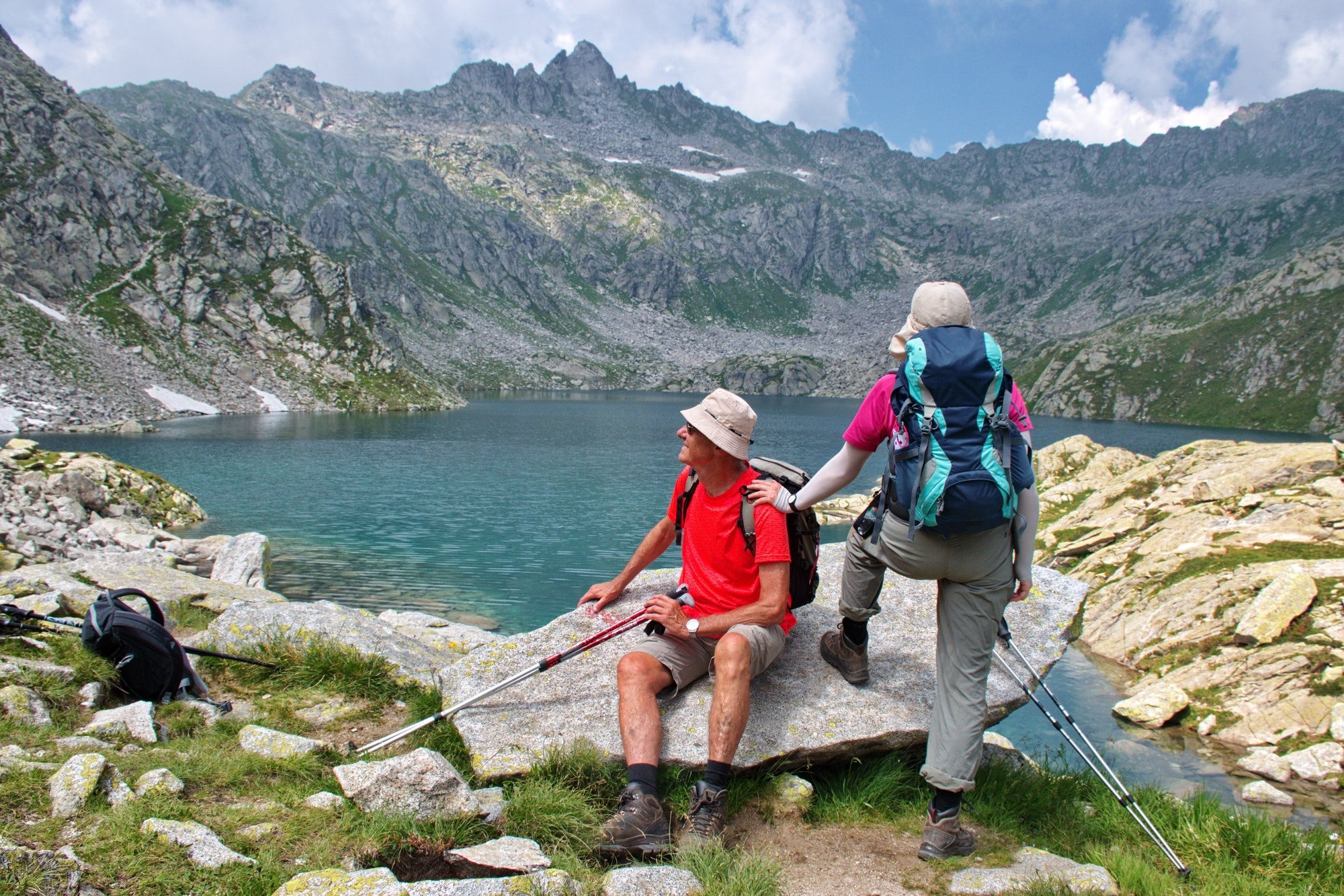 Senior couple looking at the lake in Brenta Dolomites, Italy. Scenic rocky environment